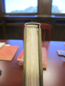 Clear view of the headband and flat back of the spine. The text block is not rounded. This method of binding suits thinner editions best, because the weight of the text block does not sag from the hinges.