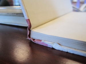 The hinge inside the front cover demonstrates the single sheet of paper that extends from the text block to cover, onto which it is pasted down. The flat spine is also evidence.