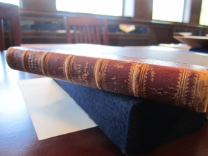 Detail of spine, in where the rounded spine is apparent, as well as the raised cords around which the textblock is sewn and through which the boards are laced. This is a great example of the raised cord binding style.