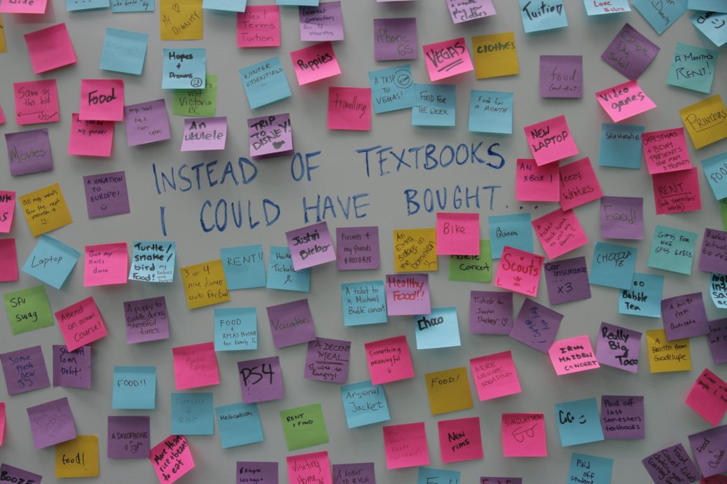 "board covered in post-its answering the question ""Instead of textbooks I could have bought..."""