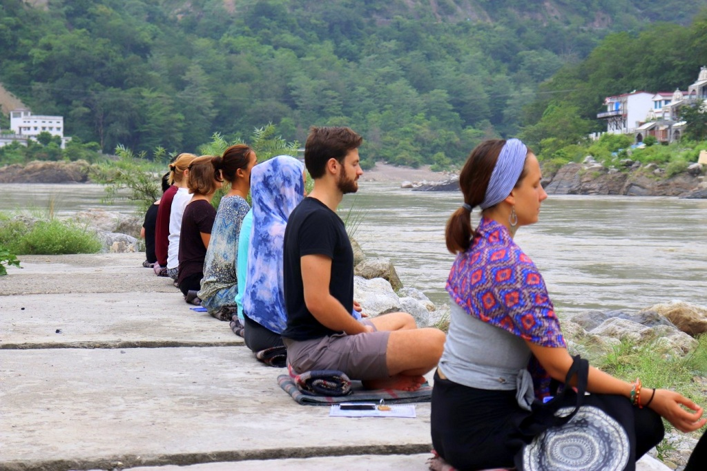 Image of people meditating near a body of water