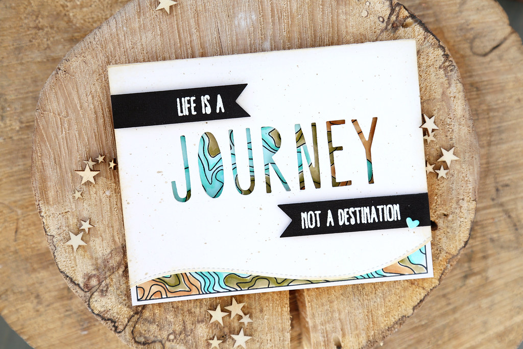 """Image of a card on a wooden base. Text reads """"life is a journey, not a destination"""""""